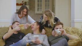 Η ομάδα καυκάσιων νέων χαλαρώνει στον καναπέ στο σπίτι και τον καφέ κατανάλωσης φιλμ μικρού μήκους