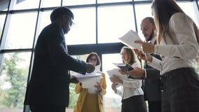 Η ομάδα μιας νεολαίας έντυσε αυστηρά τους επιχειρηματίες που στέκονται μαζί με τα οικονομικά έγγραφα στο σύγχρονο γραφείο απόθεμα βίντεο