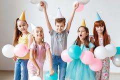 Η ομάδα μικρών παιδιών έχει τη γιορτή γενεθλίων, φορά τα εορταστικά καπέλα, κρατά τα μπαλόνια, έχει τη χαρά μαζί, απολαμβάνει τα  Στοκ εικόνα με δικαίωμα ελεύθερης χρήσης