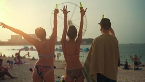 Η ομάδα νέων βάζει τα χέρια επάνω στην παραλία στο ηλιοβασίλεμα απόθεμα βίντεο