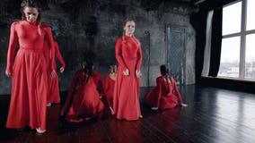 Η ομάδα νέων κοριτσιών χορευτών φορά πολύ τα κόκκινα φορέματα προετοιμάζει στη σκοτεινή αίθουσα, εκτέλεση φιλμ μικρού μήκους
