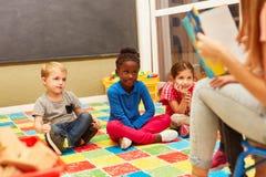 Η ομάδα παιδιών ακούει προσεκτικά διαβάζοντας μεγαλοφώνως στοκ εικόνα με δικαίωμα ελεύθερης χρήσης