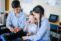 Η ομάδα παιδιών επιλέγει τα μέρη των ρομποτικών παιχνιδιών για την οικοδόμηση των ρομπότ στο σχολικό μάθημα στοκ φωτογραφίες με δικαίωμα ελεύθερης χρήσης