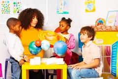 Η ομάδα παιδιών μαθαίνει τους πλανήτες στην κατηγορία παιδικών σταθμώ στοκ εικόνες