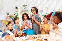 Η ομάδα παιδιών χαίρεται του κέικ με να καψει τα κεριά περιστασιακά των γενεθλίων η ευτυχής μικρογραφία ατόμων εκμετάλλευσης ημερ Στοκ εικόνα με δικαίωμα ελεύθερης χρήσης
