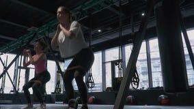 Η ομάδα συγκεντρωμένων γυναικών που απασχολούνται σκληρά να κάνει κάθεται οκλαδόν με το πόδι που ανυψώνει στη γυμναστική με το με απόθεμα βίντεο