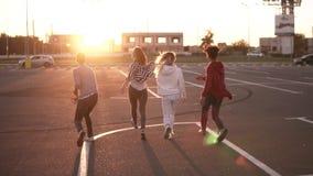 Η ομάδα τεσσάρων μοντέρνων φίλων τρέχει από την κενή ζώνη χώρων στάθμευσης υπαίθρια - η ευτυχία διασκέδασης, οι νεαροί άνδρες και απόθεμα βίντεο