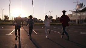 Η ομάδα τεσσάρων φίλων τρέχει από την κενή ζώνη χώρων στάθμευσης υπαίθρια - η ευτυχία διασκέδασης, οι νεαροί άνδρες και οι γυναίκ απόθεμα βίντεο