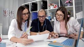 Η ομάδα του γιατρού εξετάζει τα αποτελέσματα της ανάλυσης των ασθενών στο γραφείο φιλμ μικρού μήκους