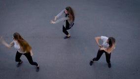 Η ομάδα τριών θηλυκών χορευτών χορεύει σε μια οδό το βράδυ, άποψη στους αριθμούς τους από την κορυφή απόθεμα βίντεο