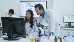 Η ομάδα των επιστημόνων ιατρικής έρευνας εργάζεται στους υπολογιστές στο σύγχρονο εργαστήριο φιλμ μικρού μήκους