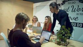 Η ομάδα των νέων επιτυχών επιχειρηματιών που απασχολούνται σε ένα νέο ξεκίνημα και συζητά τις νέες ιδέες στην αίθουσα συνεδριάσεω φιλμ μικρού μήκους