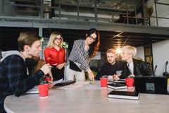 Η ομάδα των νέων επιχειρησιακών επαγγελματιών που χρησιμοποιούν την τεχνολογία σε μια άτυπη συνεδρίαση δέσμευσε στο σχέδιο αρχιτε στοκ εικόνα με δικαίωμα ελεύθερης χρήσης