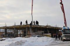 Η ομάδα των οικοδόμων που εργάζονται στην οικοδόμηση του κτηρίου στο Novosibirsk, το χειμώνα του χυμένου σκυροδέματος που χρησιμο στοκ φωτογραφία με δικαίωμα ελεύθερης χρήσης