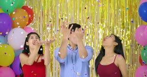 Η ομάδα φίλων απολαμβάνει με το κομφετί πέρα από το χρυσό ακτινοβολεί υπόβαθρο φιλμ μικρού μήκους