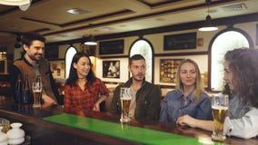 Η ομάδα φίλων κάθεται στο μετρητή και την ομιλία φραγμών Τα γυαλιά μπύρας και τα μπουκάλια, πίνακες είναι ορατά Φιλικός άτυπος απόθεμα βίντεο
