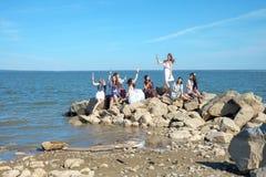 Η ομάδα ή η ομάδα πολλή όμορφα νέα ενήλικα κορίτσια χίπηδων στέκεται στο νερό στην παραλία ενώ διαφανές γυαλί λαβής με Στοκ Φωτογραφία