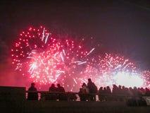 Η ομάδα ανθρώπων που απολαμβάνει τα θεαματικά κόκκινα πυροτεχνήματα παρουσιάζει σε ένα καρναβάλι ή διακοπές Στοκ Εικόνες