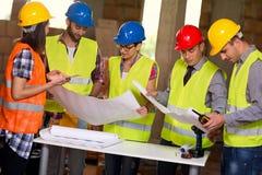 Η ομάδα αρχιτεκτόνων και οι εργάτες οικοδομών εξετάζουν την μπλε τυπωμένη ύλη Στοκ εικόνα με δικαίωμα ελεύθερης χρήσης