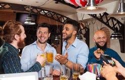 Η ομάδα ατόμων στην μπύρα κατανάλωσης φραγμών, φίλοι φυλών μιγμάτων που συναντιέται, γενειοφόρο άτομο πληρώνει με την πιστωτική κ Στοκ εικόνες με δικαίωμα ελεύθερης χρήσης