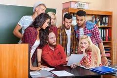 Η ομάδα γυμνασίου σπουδαστών που εξετάζει το έγγραφο εγγράφου με τον καθηγητή Sitting στο γραφείο, δάσκαλος νέων συζητά Στοκ εικόνες με δικαίωμα ελεύθερης χρήσης