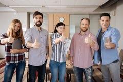 Η ομάδα ευτυχούς αύξησης ανθρώπων φυλλομετρεί επάνω στοκ φωτογραφία με δικαίωμα ελεύθερης χρήσης