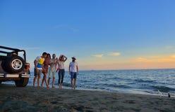 Η ομάδα ευτυχών νέων τρέχει στο υπόβαθρο της παραλίας και της θάλασσας ηλιοβασιλέματος Στοκ εικόνα με δικαίωμα ελεύθερης χρήσης
