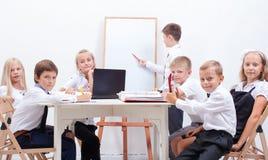 Η ομάδα εφήβων που κάθονται σε μια επιχείρηση Στοκ Εικόνες