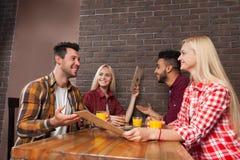 Η ομάδα νέων κάθεται στις επιλογές λαβής επιτραπέζιων φραγμών, κάνοντας τη διαταγή, τον άνδρα φυλών μιγμάτων και τη γυναίκα Στοκ Εικόνα