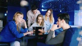 Η ομάδα νέων που χαλαρώνουν σε έναν καφέ ή ένα εστιατόριο, χρησιμοποιεί την ταμπλέτα, το oschayutsya, το κρασί κατανάλωσης ή τη σ απόθεμα βίντεο