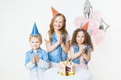 Η ομάδα παιδιών στα εορταστικά καλύμματα χτυπά τα χέρια τους κοντά στο κέικ γενεθλίων, μπαλόνια στο υπόβαθρο Στοκ φωτογραφία με δικαίωμα ελεύθερης χρήσης