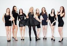Η ομάδα πολλοί δροσίζει τους σύγχρονους φίλους κοριτσιών στο διαφορετικό μαύρο φόρεμα ύφους μόδας μαζί που έχει τη διασκέδαση στο Στοκ Φωτογραφία