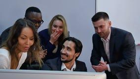 Η ομάδα πολυφυλετικής επιχειρησιακής ομάδας με το αποτέλεσμα, έκπληκτο, που χαμογελά και που εξετάζει το φορητό προσωπικό υπολογι φιλμ μικρού μήκους