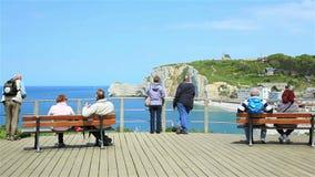 Η ομάδα τουριστών απολαμβάνει τη θέα των διάσημων απότομων βράχων Etretat απόθεμα βίντεο