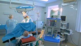 Η ομάδα του χειρούργου σε ομοιόμορφο εκτελεί τη λειτουργία σε έναν ασθενή στη χειρουργική επέμβαση φιλμ μικρού μήκους