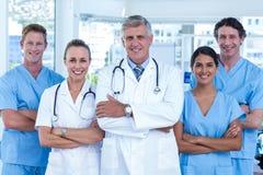 Η ομάδα των γιατρών που στέκονται οπλίζει διασχισμένος και χαμογελώντας στη κάμερα Στοκ εικόνες με δικαίωμα ελεύθερης χρήσης