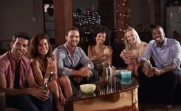 Η ομάδα φίλων σε ένα κόμμα σπιτιών κάθεται το κοίταγμα στη κάμερα στοκ εικόνες