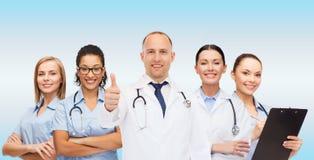 Η ομάδα χαμογελώντας γιατρών με την παρουσίαση φυλλομετρεί επάνω Στοκ φωτογραφία με δικαίωμα ελεύθερης χρήσης