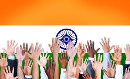 Η ομάδα Multiethnic οπλίζει αυξημένος και μια σημαία της Ινδίας στοκ φωτογραφία