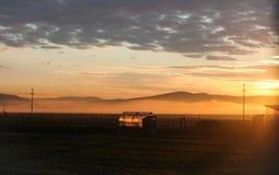 Η ομίχλη στην κοιλάδα και ένα θερμοκήπιο φωτίζεται από τον ήλιο πέρα από τα βουνά στοκ εικόνα με δικαίωμα ελεύθερης χρήσης
