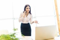 Η ομιλία επιχειρησιακών γυναικών με κινητό τηλέφωνο και εξετάζει το lap-top ενάντια στο παράθυρο στην αρχή Στοκ φωτογραφίες με δικαίωμα ελεύθερης χρήσης