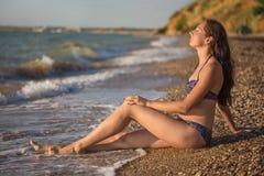 Η ονειροπόλος γυναίκα κάθεται στην κυματωγή θάλασσας Στοκ Φωτογραφία