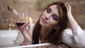 Η ονειροπόλος νέα γυναίκα στο άσπρο πουκάμισο πίνει το κόκκινο κρασί από την υψηλή συνεδρίαση γυαλιού στο luxary λουτρό και χαμογ απόθεμα βίντεο