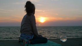 Η ονειροπόλος συνεδρίαση μικρών κοριτσιών στην ακτή και φαίνεται θαυμάσιο ηλιοβασίλεμα, ενυδρείο με το υπαίθριο περιβάλλον έννοια απόθεμα βίντεο