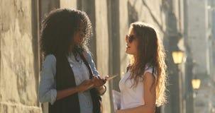 Η οριζόντια υπαίθρια άποψη των δύο όμορφων πολυπολιτισμικών σπουδαστών που μιλούν κατά τη διάρκεια της ηλιόλουστης ημέρας φιλμ μικρού μήκους