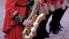 Η ορχήστρα πνευστ0ών από χαλκό Kostanay Κορίτσια στα κόκκινα ενδύματα ουσάρων και το μαύρο παιχνίδι μποτών saxophones Κινηματογρά απόθεμα βίντεο