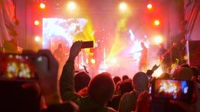 Η ορχήστρα ροκ, πολλά χέρια με κινητό κάνει τις αποδόσεις φωτογραφιών στο αναμμένο στάδιο απόθεμα βίντεο