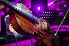 Η ορχήστρα στο βιολί πρόβας και το ροδανιλίνης ελαφρύ υπόβαθρο στοκ εικόνα με δικαίωμα ελεύθερης χρήσης