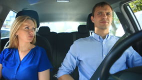 Η οδήγηση ζεύγους στο αυτοκίνητο, ένας άνδρας και μια γυναίκα οδηγούν μαζί στο αυτοκίνητο μέσω των οδών της πόλης και κοιτάζουν γ φιλμ μικρού μήκους