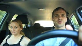 Η οδήγηση ζεύγους στο αυτοκίνητο, ένας άνδρας και μια γυναίκα οδηγούν μαζί στο αυτοκίνητο μέσω των οδών της πόλης και χαρωπά της  απόθεμα βίντεο